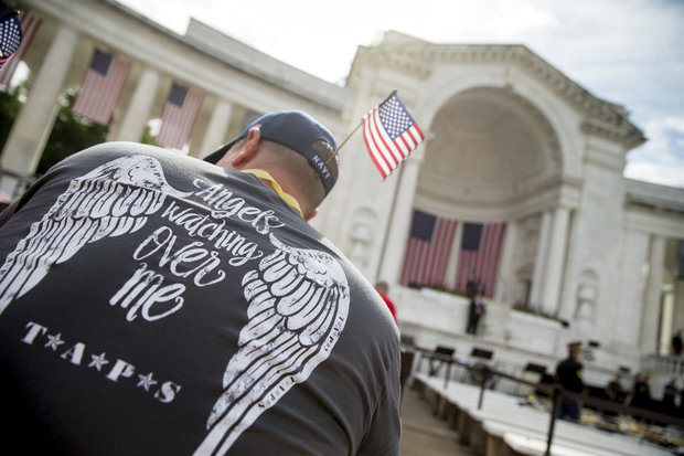 Chris Payne of Kalama, Washington, wears a Tragedy Assistance Program for Survivors (TAPS) shirt depicting wings on his back as he and other guests wait for President Barack Obama to speak at the Memorial Amphitheater of Arlington National Cemetery, in Arlington, Va., Monday, May 30, 2016, during a Memorial Day ceremony. (AP Photo/Andrew Harnik, File)